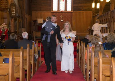 smiling bride & groom walking hand in hand down aisle with groom carrying toddler son