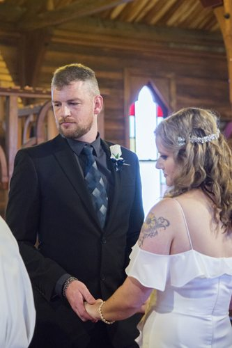 serious looking bride & groom holding hands and looking towards vicar in historic wooden church