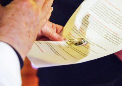 closeup of vicar blessing wedding rings