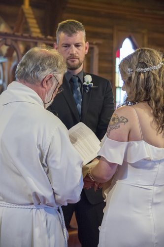 serious looking groom with vicar reading vows in historic wooden church