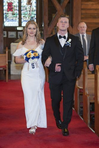 bride & son walking down aisle in historic wooden church with leadlight windows