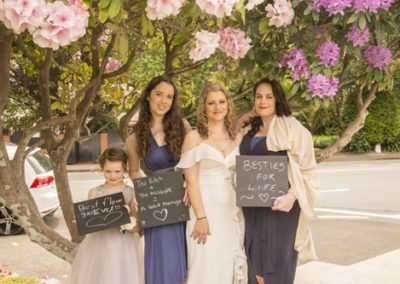 bride & ladies with blackboards under pink rhododendron bushes