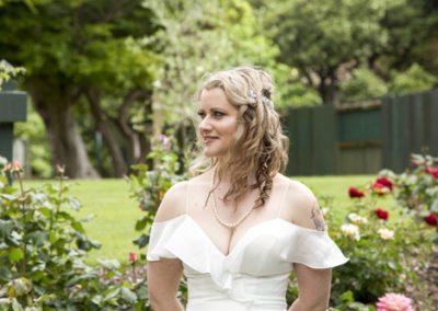 windswept bride outdoors in rosegarden