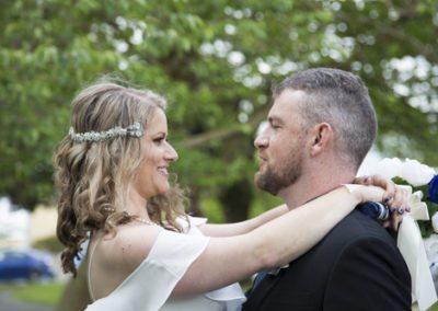 closeup of happy bride & groom embracing outdoors in bush setting