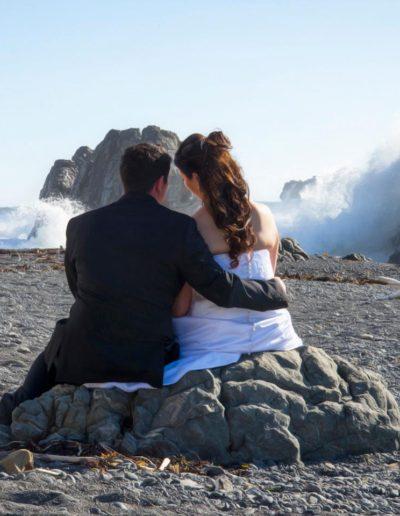 Pencarrow Lodge wedding bride & groom sit on rocks on beach watching large surf