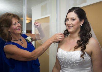 Bride's mum adjusting smiling bride's veil, before Pencarrow Lodge wedding