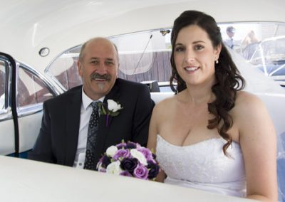 Smiling bride & dad in back of classic car on way to Pencarrow Lodge wedding