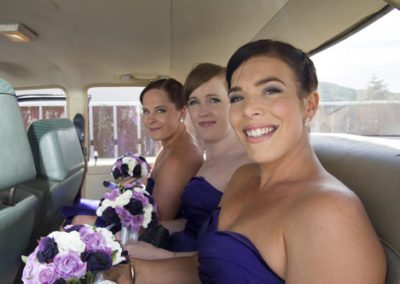 smiling bridesmaids in back of classic car on way to Pencarrow Lodge wedding