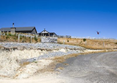 Pencarrow Lodge viewed from road below, with groomsmen helicopter landing under a bright blue sky