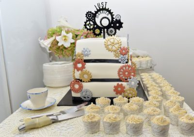 cogs & gears themed wedding cake surrounds by cupcakes