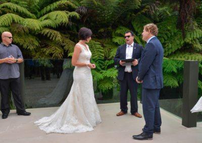 bride & groom with celebrant speaking in native bush setting