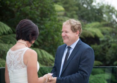 bride & groom holding hands with bride reading vows in native bush setting