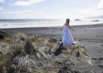 Pencarrow Lodge wedding bride spinning on beach as wind blows tussock grass wildly