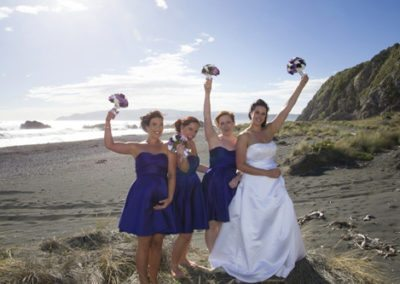 Pencarrow Lodge wedding bride & bridesmaids raise their bouquets and cheer on beach