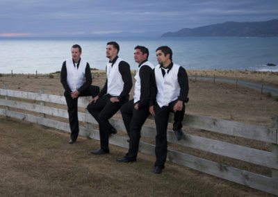 Pencarrow Lodge wedding groom & groomsmen sitting on rustic wooden fence at sunset, with Wellington hills in background