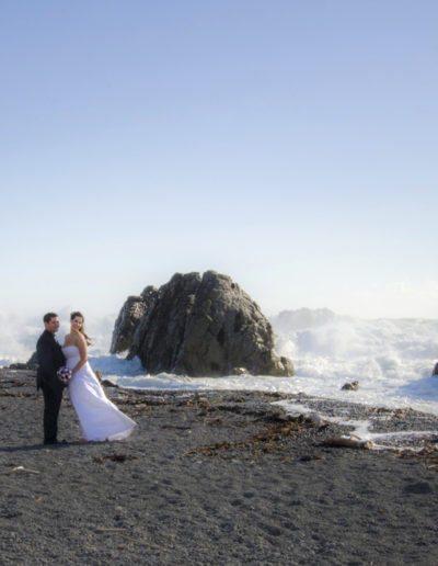 Pencarrow Lodge wedding windswept bride & groom stand on beach with huge surf breaking