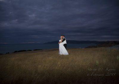 Bride & groom embrace on hilltop at night, Wellington hills behind Pencarrow Lodge wedding