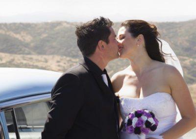 Pencarrow Lodge wedding closeup of happy bride & groom kissing by classic car
