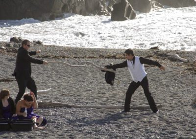 Pencarrow Lodge wedding groomsmen play with driftwood swords on beach as bridesmaids watch from picnic blanket