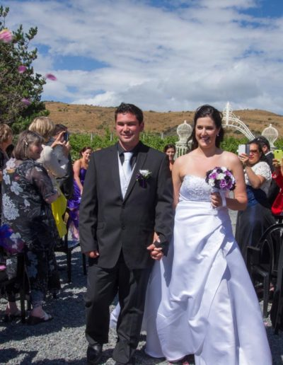 Pencarrow Lodge wedding smiling bride & groom walk hand in hand down aisle as guests take photos