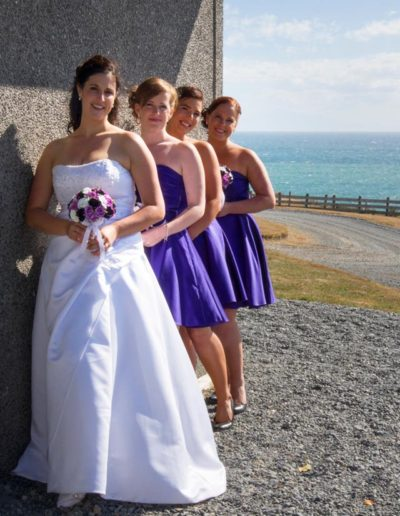Pencarrow Lodge wedding bride & bridesmaids lined up against side of lodge, with choppy sea in background