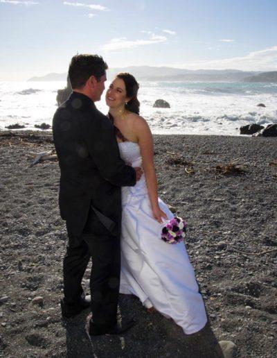 Pencarrow Lodge wedding bride & groom embrace on windy beach