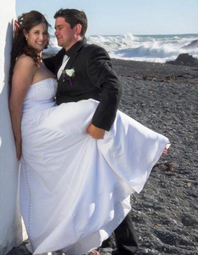Pencarrow Lodge wedding saucy bride & groom with leg raised leaning against lighthouse