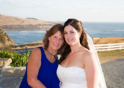Pencarrow Lodge wedding bride & mum embracing in sunshine, with beautiful coastline behind