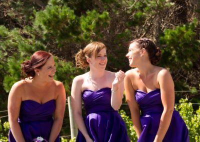 Pencarrow Lodge wedding laughing bridesmaids in purple dresses with trees in background