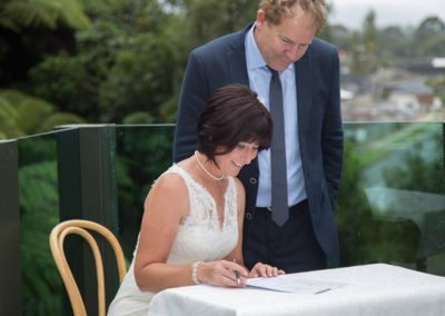 smiling bride signing register outdoors, with groom watching on