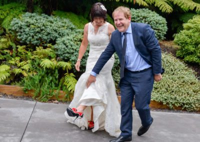 laughing groom lifting wedding gown to show bride's special red and black stiletto shoes