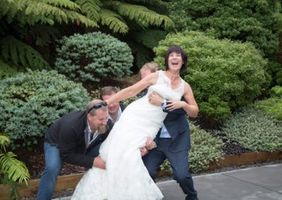 laughing bride being picked up by groom and her brothers in bush setting
