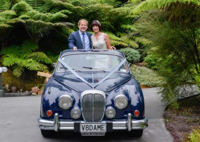 smiling bride & groom standing in Daimler car sunroof in native bush setting