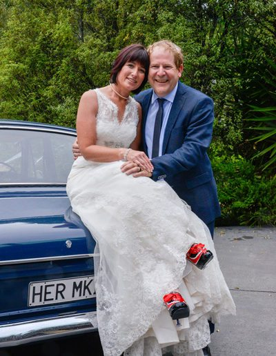 bride & groom embracing, with bride sitting on her mk II car, & showing red & black shoes