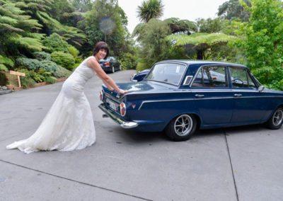 smiling bride pushing old blue mk II car in bush setting