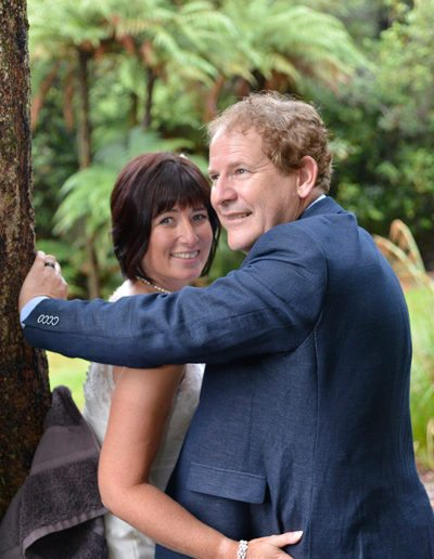 bride & groom in native bush setting embracing while leaning against tree