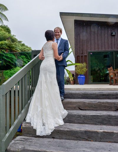 bride & groom romantically embracing on outdoor stairs, good view of gown train