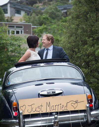 bride & groom standing up through Daimler sunroof, smiling happily at each other, and Just married sign on back of car
