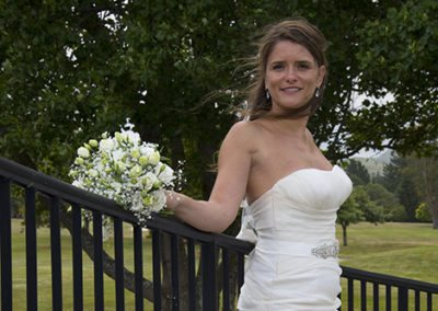 Closeup of windswept sexy bride leaning against fence